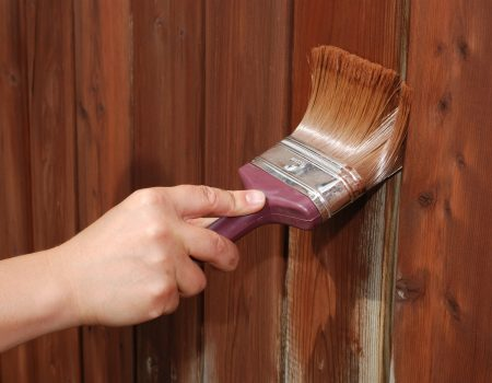 A picture of a woman painting fence